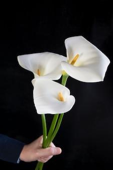 Beau bouquet de callas blancs dans les mains des hommes sur une orientation verticale noire