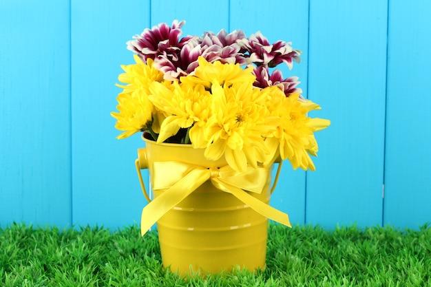 Beau bouquet de chrysanthèmes dans un seau coloré lumineux sur fond de clôture bleue