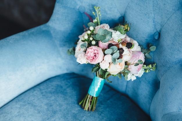 Beau bouquet de couleur se dresse sur le fauteuil bleu intérieur