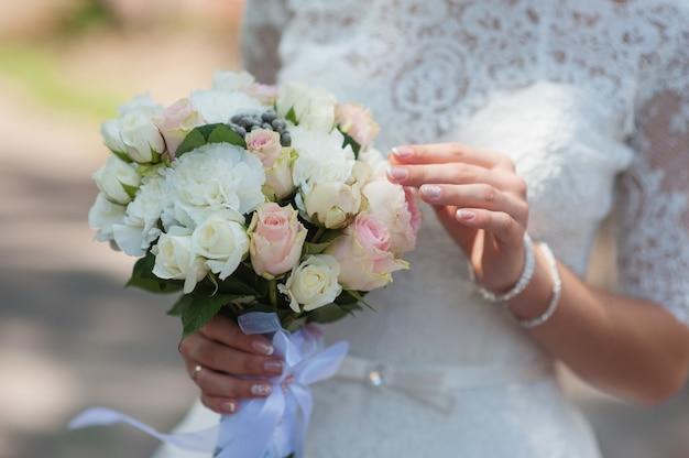Beau bouquet dans les mains de la mariée le jour du mariage