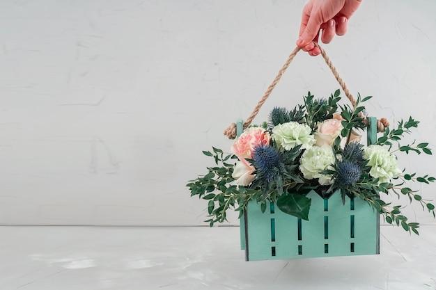 Beau bouquet dans un panier. main tient un bouquet dans une boîte design.