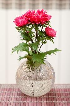 Beau bouquet de fleurs d'aster rouge dans un vase en cristal sur une serviette en bois avec un arrière-plan flou. faible profondeur de champ.