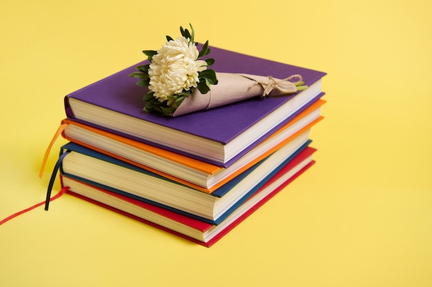 Beau bouquet de fleurs d'asters d'automne dans du papier d'emballage artisanal attaché en corde allongé sur des livres multicolores empilés. concept de la journée des enseignants, littéraire, connaissance, éducation. espace de copie de fond jaune