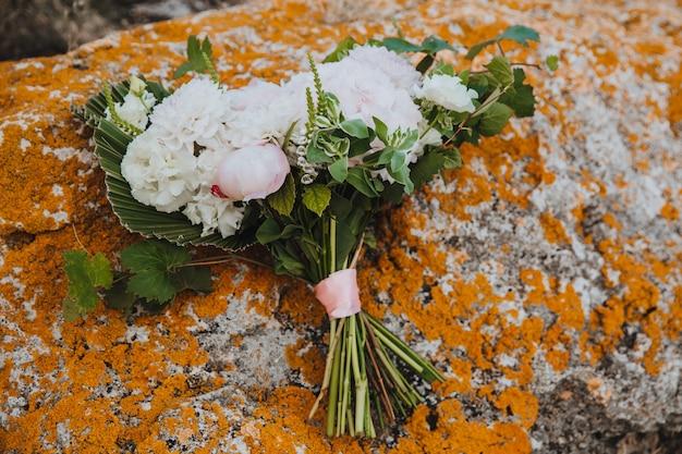 Un beau bouquet de fleurs attaché avec un ruban rose se trouve sur une pierre avec de la mousse