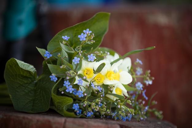 Beau bouquet de fleurs de jardin de myosotis et de narcisses sur le fond en bois