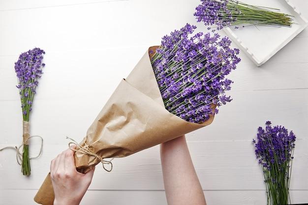Beau bouquet de fleurs de lavande naturel enveloppé dans du papier dans les mains de la femme sur bois blanc