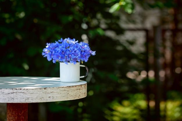Beau bouquet de fleurs de maïs bleu d'été en pot blanc sur la nature