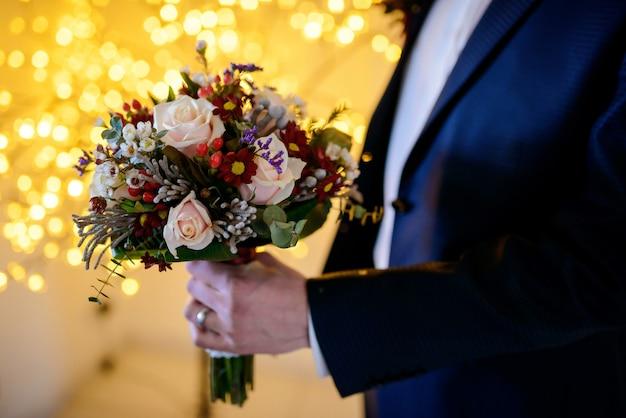 Beau bouquet de fleurs mélangées dans la main d'un marié en costume sur jaune