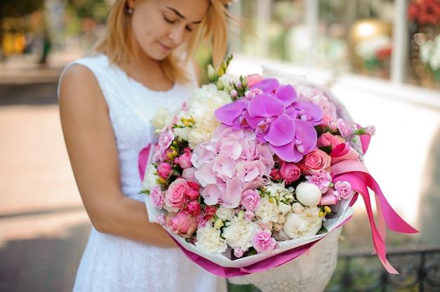 Beau bouquet de fleurs mélangées détenu par une femme