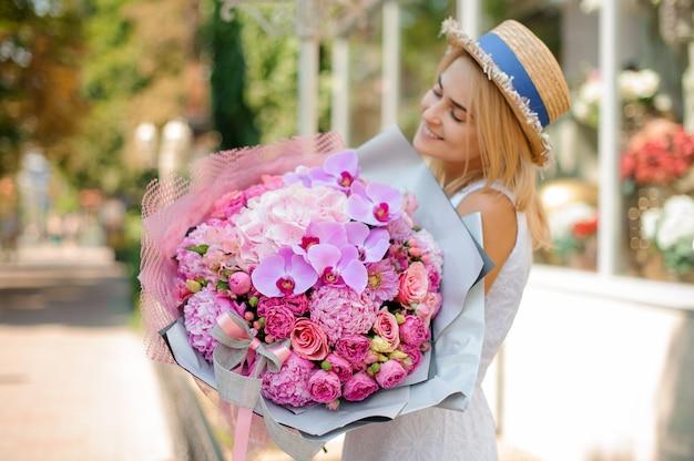 Beau bouquet de fleurs mixtes tenir par une femme souriante. mise au point sélective