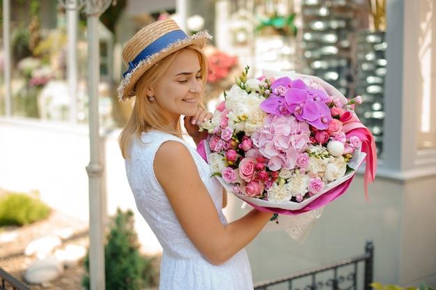 Beau bouquet de fleurs mixtes tenir par une femme souriante