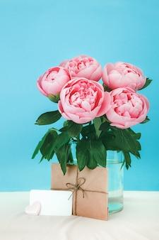 Beau bouquet de fleurs de pivoine rose dans un vase en verre sur fond cyan. gouttes d'eau sur le pétale de pivoines.