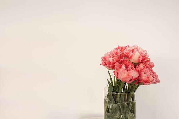 Beau bouquet de fleurs de pivoine rose dans un vase en verre sur table en marbre blanc