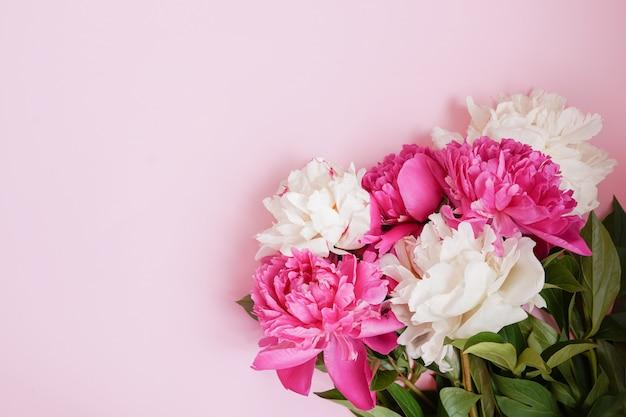 Beau bouquet de fleurs de pivoines sur mur rose, espace copie