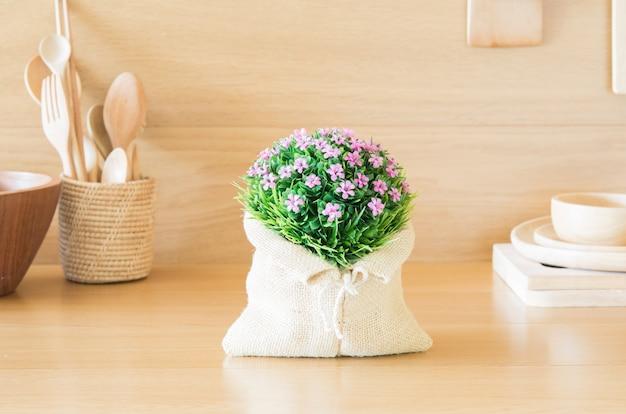 Beau bouquet de fleurs en plastique dans la cuisine en bois.