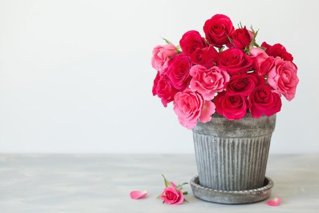 Beau bouquet de fleurs de rose rouge dans un vase sur blanc