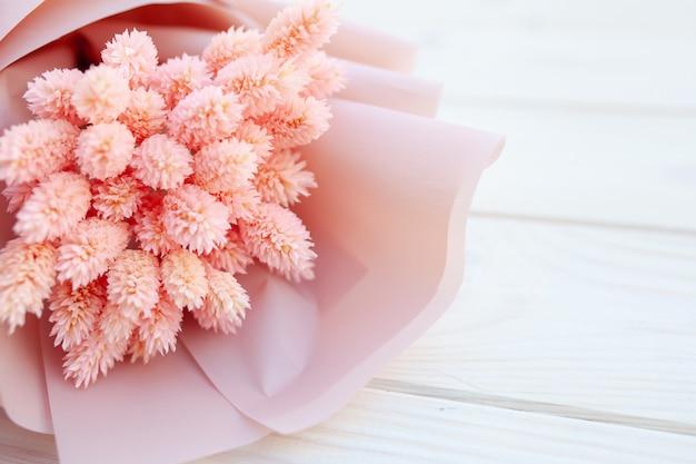 Beau bouquet de fleurs roses sèches sur blanc en bois