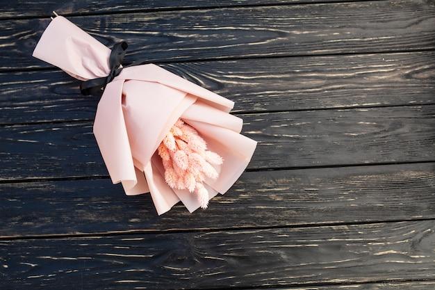 Beau bouquet de fleurs roses sèches sur un fond noir en bois.