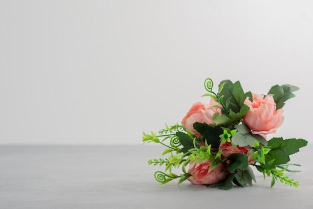 Beau bouquet de fleurs roses sur table grise.