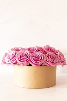 Beau bouquet floral avec des roses roses dans une boîte sur fond rose