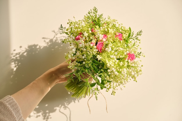 Beau bouquet frais de fleurs de muguet, rose rose, branches vertes dans la main de la femme