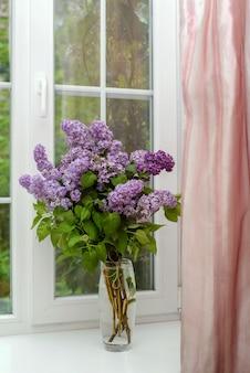 Beau bouquet de lilas violet dans un vase en verre sur un rebord de fenêtre blanc