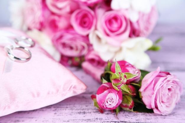 Beau bouquet de mariage et coussin avec anneaux sur bois