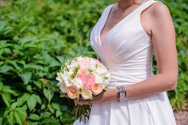 Beau bouquet de mariage de délicates roses roses et blanches dans les mains de la mariée dans une robe blanche gros plan