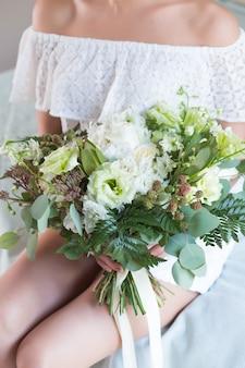Beau bouquet de mariage avec différentes fleurs sur les mains de la mariée.