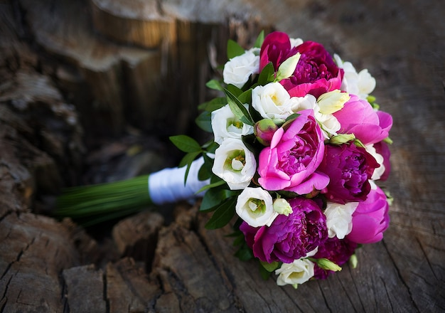 Beau bouquet de mariage avec des fleurs colorées allongé sur une souche d'arbre.
