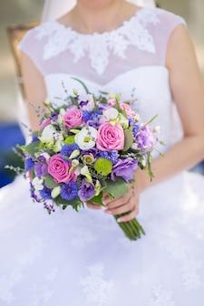 Beau bouquet de mariage de fleurs fraîches entre les mains de la mariée