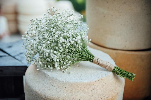 Un beau bouquet de mariage de gypsophile repose sur une cruche en argile.