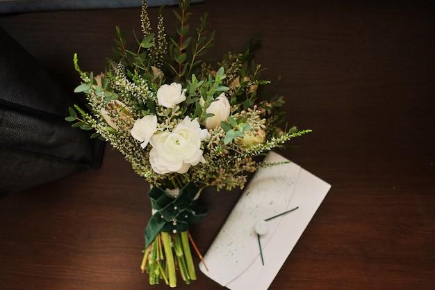 Beau bouquet de mariage se trouve sur un fond en bois, à une pochette blanche