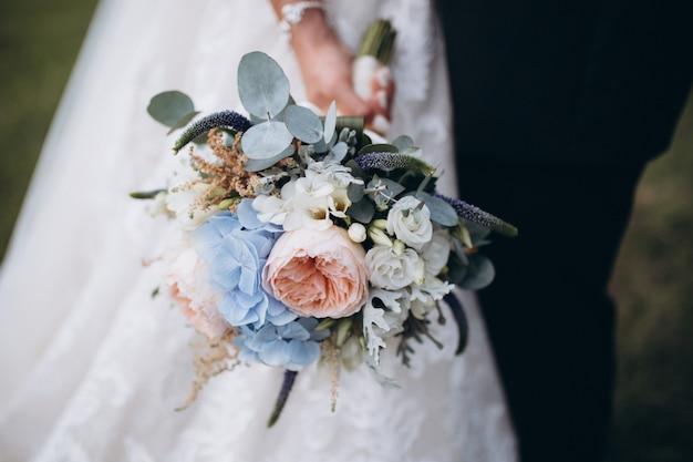 Beau bouquet de mariée avec des fleurs rouges, roses et blanches, des roses et des eucalyptus, des pivoines, des lis calla