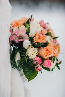 Beau bouquet de mariée avec des roses blanches et oranges et des alstroemerias roses