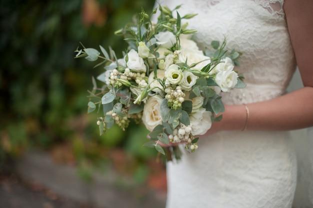 Beau bouquet moderne de mariée dans les mains de la mariée