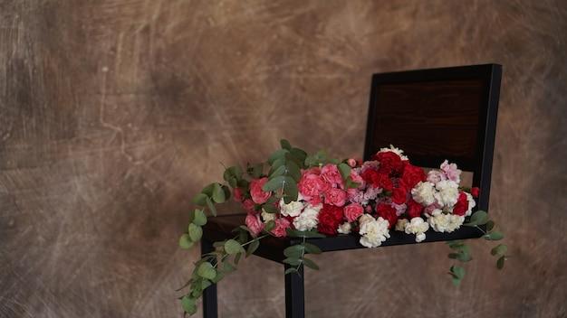 Beau bouquet d'oeillets roses et blancs. bouquet avec des brins verts se trouve sur un fond texturé sombre