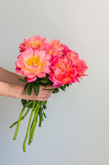 Beau bouquet de pivoines roses dans la main d'un homme sur un fond de mur blanc