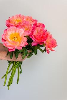 Beau bouquet de pivoines roses dans la main d'un homme sur fond de mur blanc