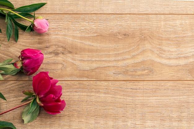 Beau bouquet de pivoines rouges et roses sur fond en bois. vue de dessus avec espace de copie.