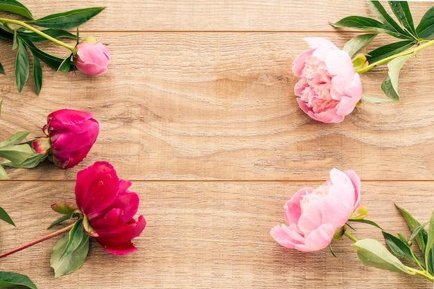 Beau bouquet de pivoines rouges et roses sur fond en bois. vue de dessus.