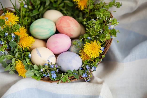 Un beau bouquet de printemps dans un panier en bois avec des oeufs de pâques peints à l'aquarelle