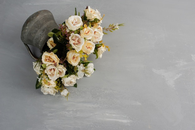 Beau bouquet de roses blanches sur une surface grise