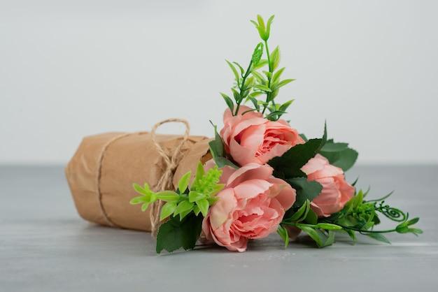 Beau bouquet de roses roses sur surface grise