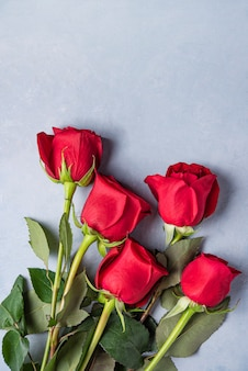 Beau bouquet de roses rouges se trouve sur un fond bleu saint valentin. vue de dessus et espace de copie