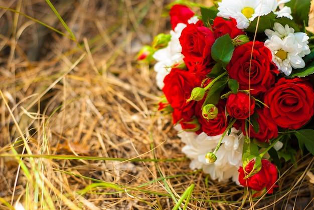 Beau bouquet de roses rouges vives et de marguerites blanches