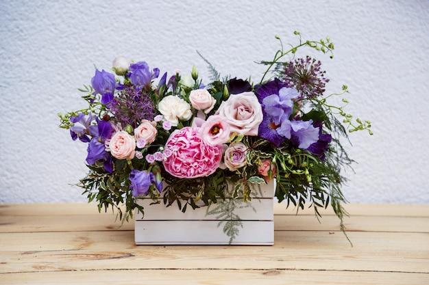 Beau bouquet tendre de pivoines dans une boîte en bois sur une table rustique