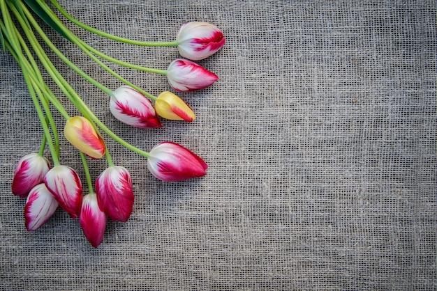 Beau bouquet de tulipes colorées rose vif et jaune sur la surface de la toile