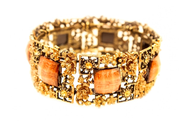 Beau bracelet en métal jaune avec pierres carrées isolé sur fond blanc.