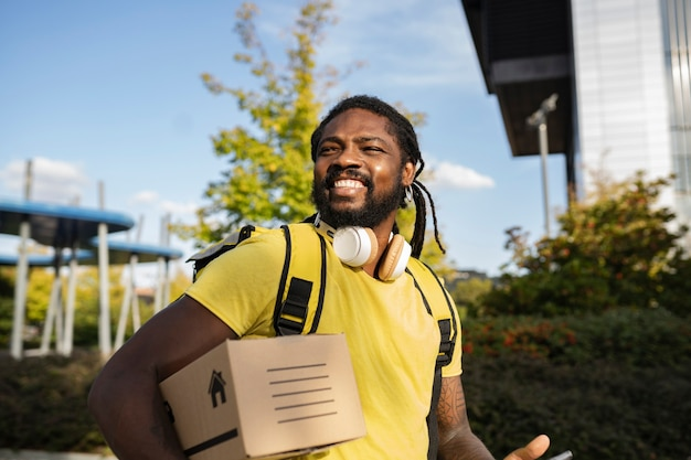 Beau brésilien avec livreur de dreadlocks avec une boîte, avec des écouteurs souriant autour de la ville